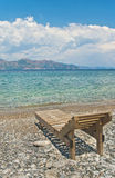 Single wooden lounge chair at pebble beach on sunny day Royalty Free Stock Photo