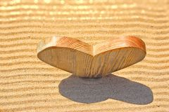 Single wooden love heart in the sand Stock Photos