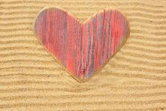 Single wooden love heart in the sand Stock Photography