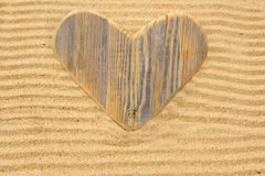 Single wooden love heart in the sand Royalty Free Stock Photos