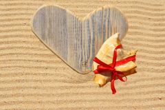 Single wooden love heart and seashell in the sand Stock Photos