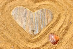 Single wooden love heart and seashell in the sand Royalty Free Stock Images