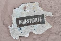 Single word Investigate. Word Investigate written on a roughly damaged wall stock images