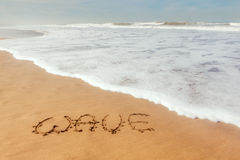 Single word wave written on sand. With ocean waves flowing Stock Images