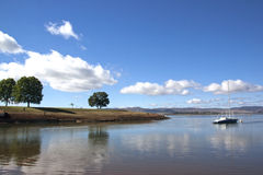 Single Yacht Anchored off the Banks of Midmar dam Stock Photo
