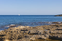 SIngle yacht oon blue sea with rocky beach Stock Images
