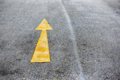 Single yellow arrow sign marking on road surface Stock Images
