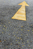 Single yellow arrow sign marking on road surface Stock Photos