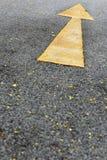 Single yellow arrow sign marking on road surface Stock Photos