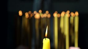 A single yellow candle that is lit in the Church and in the background a few candles set fire to the Christians and put stock footage