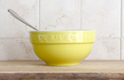 A single yellow ceramic cup with a spoon Royalty Free Stock Images