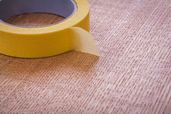 Single yellow duct tape on vintage brown wooden Royalty Free Stock Image