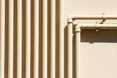 Single yellow gas, oil and water pipeline on gray or black wall.  royalty free stock photography