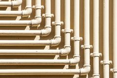 Single yellow gas, oil and water pipeline on gray or black wall.  stock images