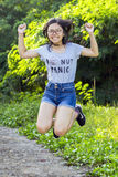Single young trendy energetic Asian lady with long hair spectacles wearing short denim jean jump for joy at park. Royalty Free Stock Images