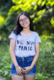 Single young trendy energetic Asian lady with long hair spectacles wearing short denim jean at park. Royalty Free Stock Photography
