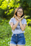 Single young trendy energetic Asian lady with long hair spectacles wearing short denim jean at park. Stock Image