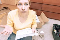 Single young woman assembling pieces of new furniture and reading the instruction, she is confused, open boxes with furniture. Details are on the floor behind stock image
