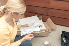 Single young woman assembling pieces of new furniture and reading the instruction, open boxes with furniture details are on the. Floor behind royalty free stock photo