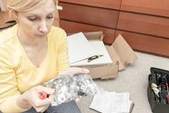 Single young woman assembling pieces of new furniture and reading the instruction, open boxes with furniture details are on the. Floor behind stock photo