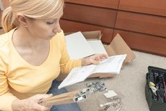 Single young woman assembling pieces of new furniture and reading the instruction, open boxes with furniture details are on the. Floor behind stock photos