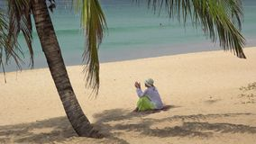 Single young woman enjoys the holiday under a palm tree on the exotic beach. UHD 4K stock footage