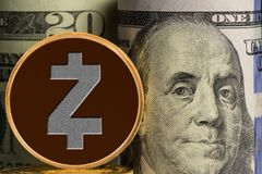 Single Zcash coin in front of bank rolls of US currency Stock Photo