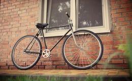 Singlespeed cykel för gammal stil mot tegelstenväggen arkivbilder