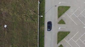 Singola automobile che muove con un recintare un il parcheggio vuoto, giorno soleggiato archivi video