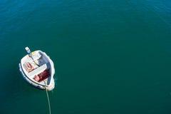 Singola barca che galleggia sul mare blu-verde Fotografia Stock