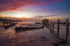 Singola barca e Boatshed di alba con il cielo bruciante Fotografia Stock Libera da Diritti