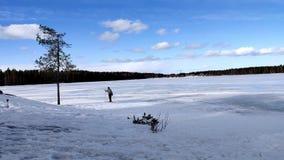 Singola corsa con gli sci della donna nel lago congelato sotto il cielo blu e la nuvola bianca archivi video