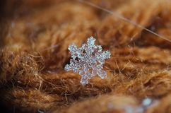 Singola macro del fiocco di neve su fondo marrone Fotografia Stock Libera da Diritti
