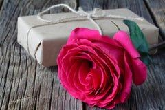 Singola rosa fresca di rosa simbolica di amore e di romance su una tavola di legno rustica per un innamorato il giorno dei biglie Immagine Stock