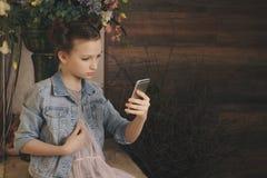 Singola tenuta teenager triste un telefono cellulare che deplora seduta sul letto nella sua camera da letto con una luce scura ne Fotografia Stock