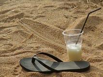 Singoli pantofola e cocktail neri della spiaggia in tazza di plastica con cannuccia sulla spiaggia nelle feste immagine stock libera da diritti