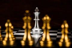 Singoli scacchi d'argento di re circondati da una serie di scacchi pi dell'oro fotografia stock