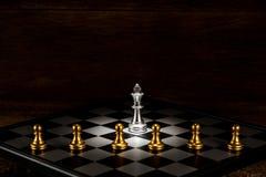 Singoli scacchi d'argento di re circondati tramite una serie di PA di scacchi dell'oro fotografie stock