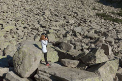 Singolo alpinista della ragazza che prende una foto in regione selvaggia Immagine Stock