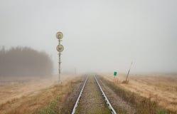 Singolo binario ferroviario che retrocede nella nebbia fotografia stock