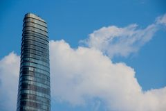 Singolo grattacielo sui precedenti luminosi del cielo fotografie stock
