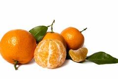 Singolo mandarino con le foglie e le fette isolate su bianco Immagine Stock