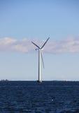 Singolo mulino a vento del mare con acqua e le nuvole blu scuro Fotografie Stock Libere da Diritti