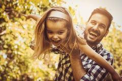 Singolo padre che gioca nel prato con la figlia Godendo nella s Fotografia Stock
