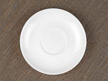 Singolo piatto bianco vuoto su tessuto grezzo o su insaccamento fotografia stock libera da diritti