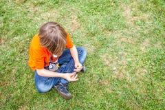 Singolo ragazzo teenager annoiato che si siede sull'erba fotografia stock libera da diritti