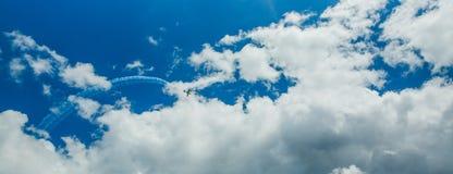 Singolo un piano di sport delle tracce acrobatiche del vapore del gruppo in cielo blu Fondo bianco piano delle piste delle tracce immagine stock libera da diritti
