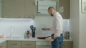 Singolo uomo che cucina omelette per la prima colazione in cucina stock footage