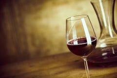 Singolo vetro di vino rosso accanto ad un decantatore fotografie stock
