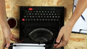 Sings typing the text of his verse on a typewriter. View from above. Sings typing the text of his verse on a typewriter, on the table is a mug of tea. View from stock footage